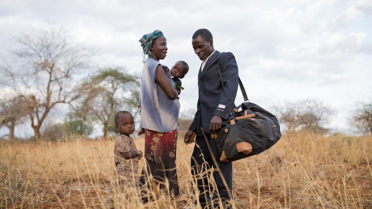 A family (mother, father and two children) standing in a dry Kenyan field.