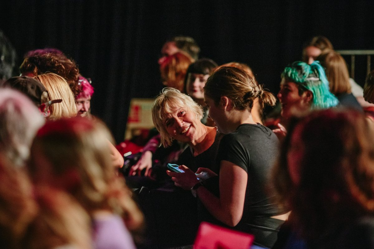 People in a darkened auditorium, smiling.