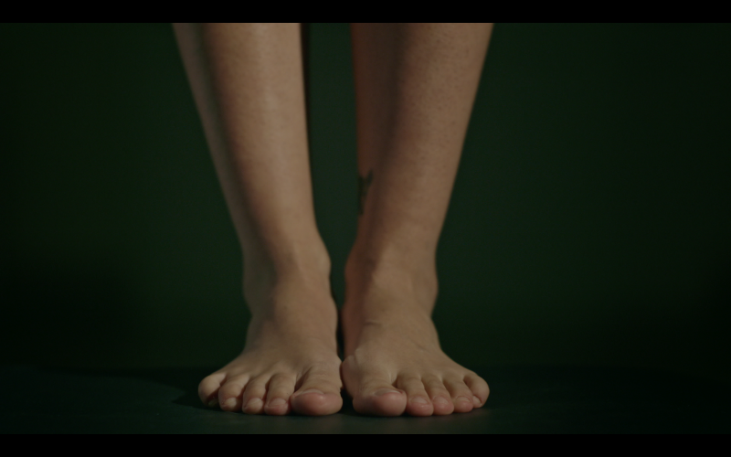 Close-up of a woman's feet and lower legs against a dark background.