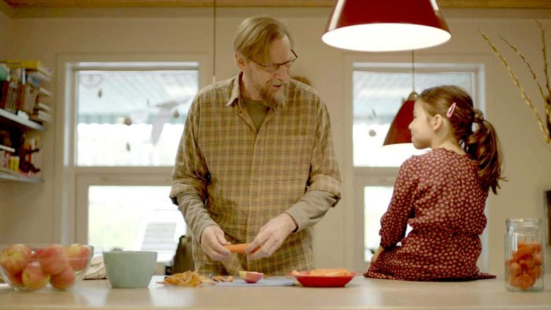 A man with a grey beard and glasses preparing food and talking to a young girl who is sitting on the countertop beside him