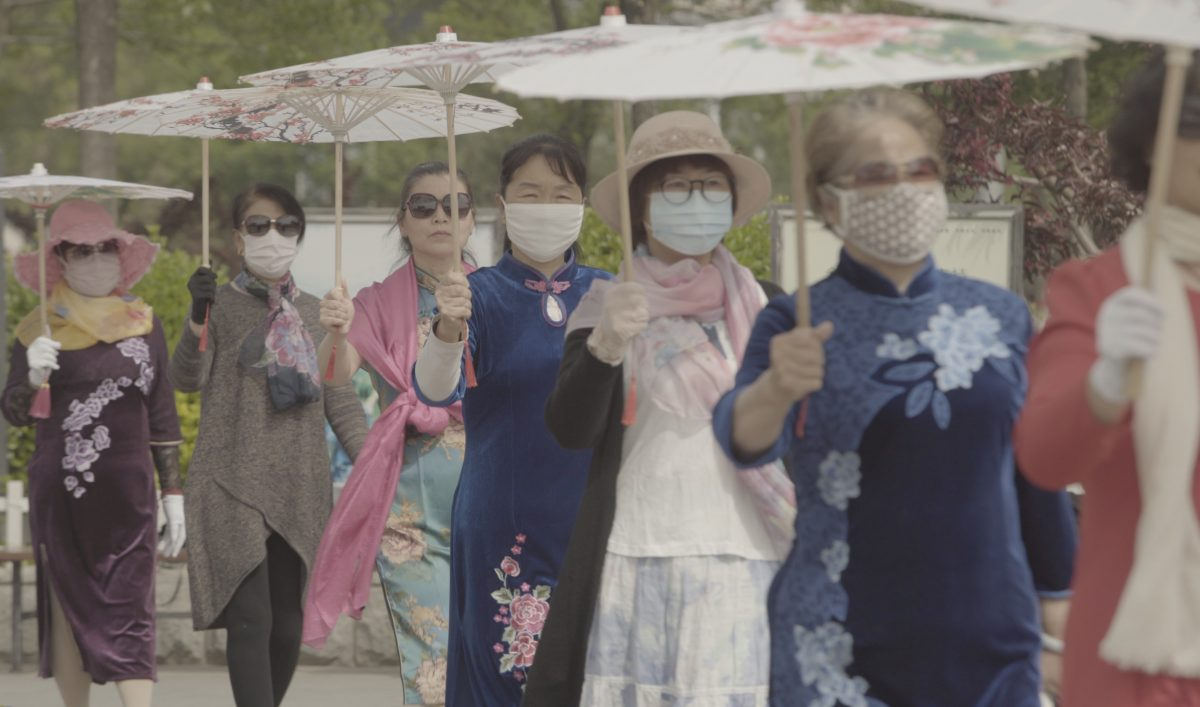 A line of women holding parasols walk down a street. All except for one are wearing masks to cover their mouth and nose.
