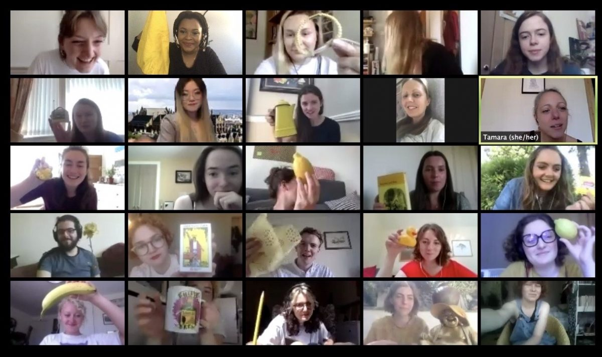 Twenty-five Take One Action staff members and volunteers on a Zoom call with each person holding a random yellow object.