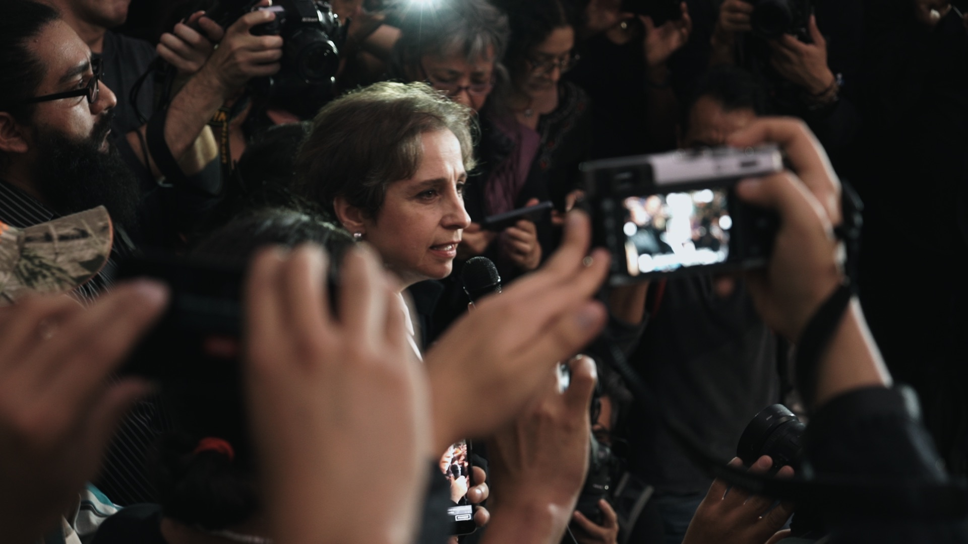 A woman in the midst of a media frenzy speaks into a microphone while journalists capture photos and videos of her.