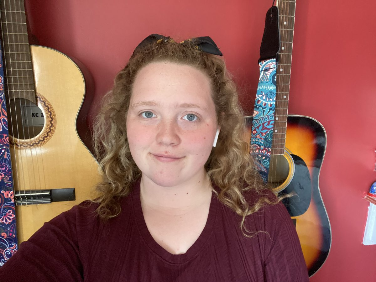 A young woman with long curly hair smiles at the camera. Behind her are two guitars hanging against a red wall.