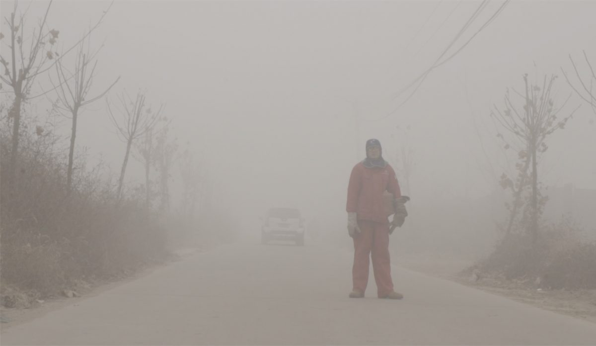 A worker in an orange worksuit stands in an empty road, with a vehicle behind them, surrounded by thick layers of smog.