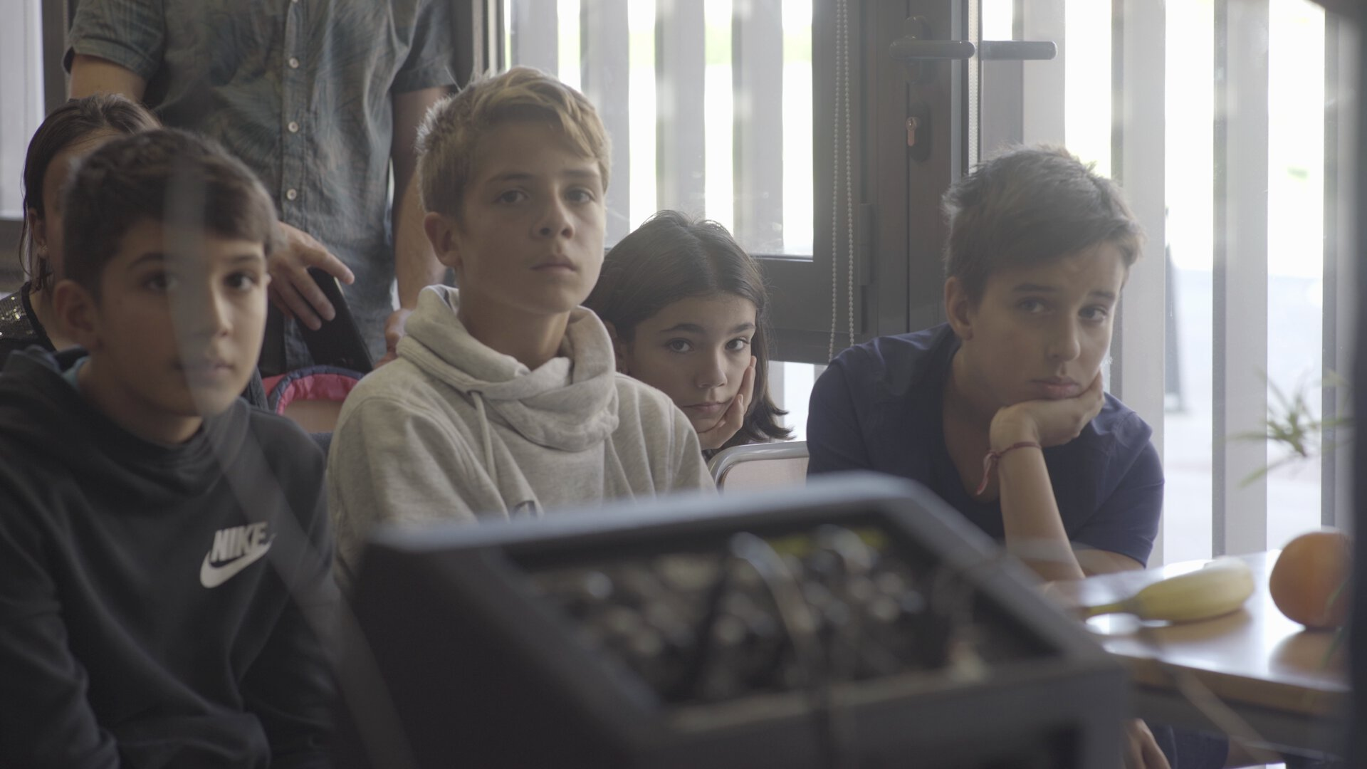Five children/teens sitting in a classroom looking beyond the camera