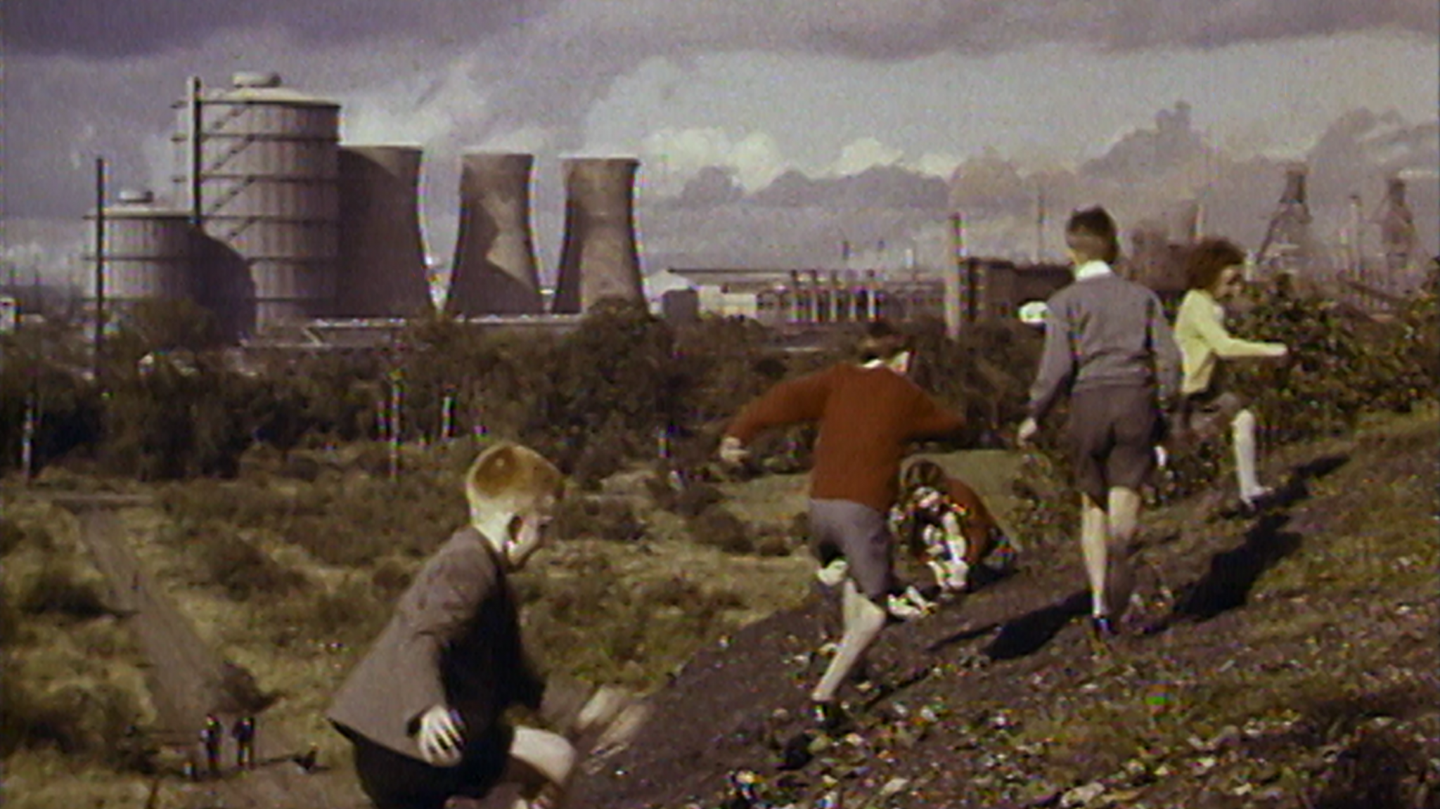 A still from footage from the 70s: children running along a hill with a massive power station in the background.
