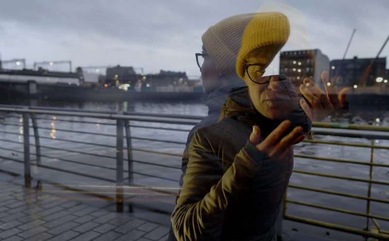 """A still from """"Affirmation #6"""". A person walks across an pedestrian bridge on a river in an industrial area. Another image of the same person is overlayed on top, this one facing the camera and holding their hands close to their face to sign. The sky is overcast and faint lights are visible from the windows of the surrounding buildings."""