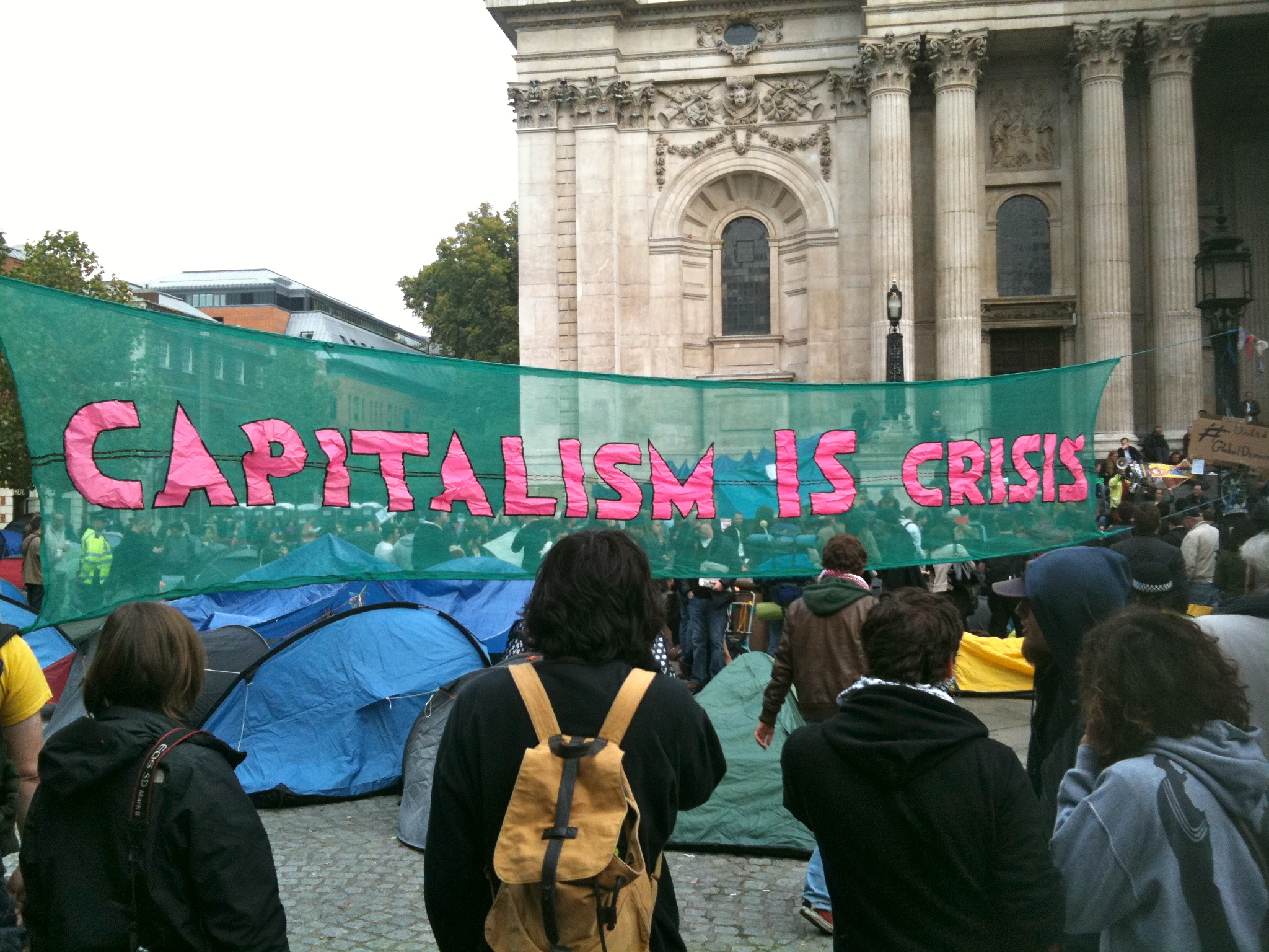 A large green banner stretches between tents and a crowd of people. Pink text in captial letters reads 'CAPITALISM IS CRISIS'