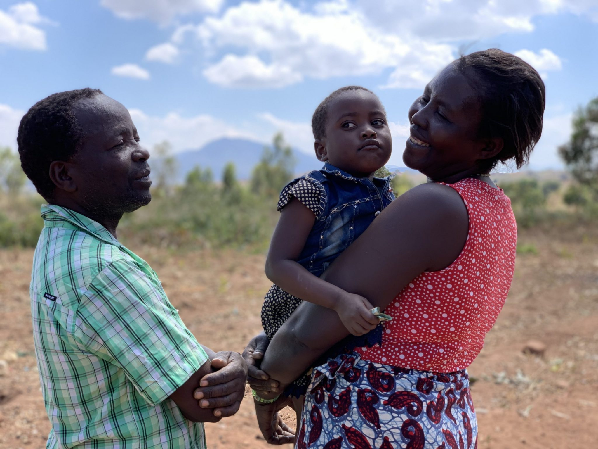 """A still from """"The Ants and the Grasshopper"""". Outdoors medium shot of Anita, the film's Malawian protagonist, holding one of her children in her arms and smiling at her husband in a dry field under a bright blue sky with a few white clouds."""