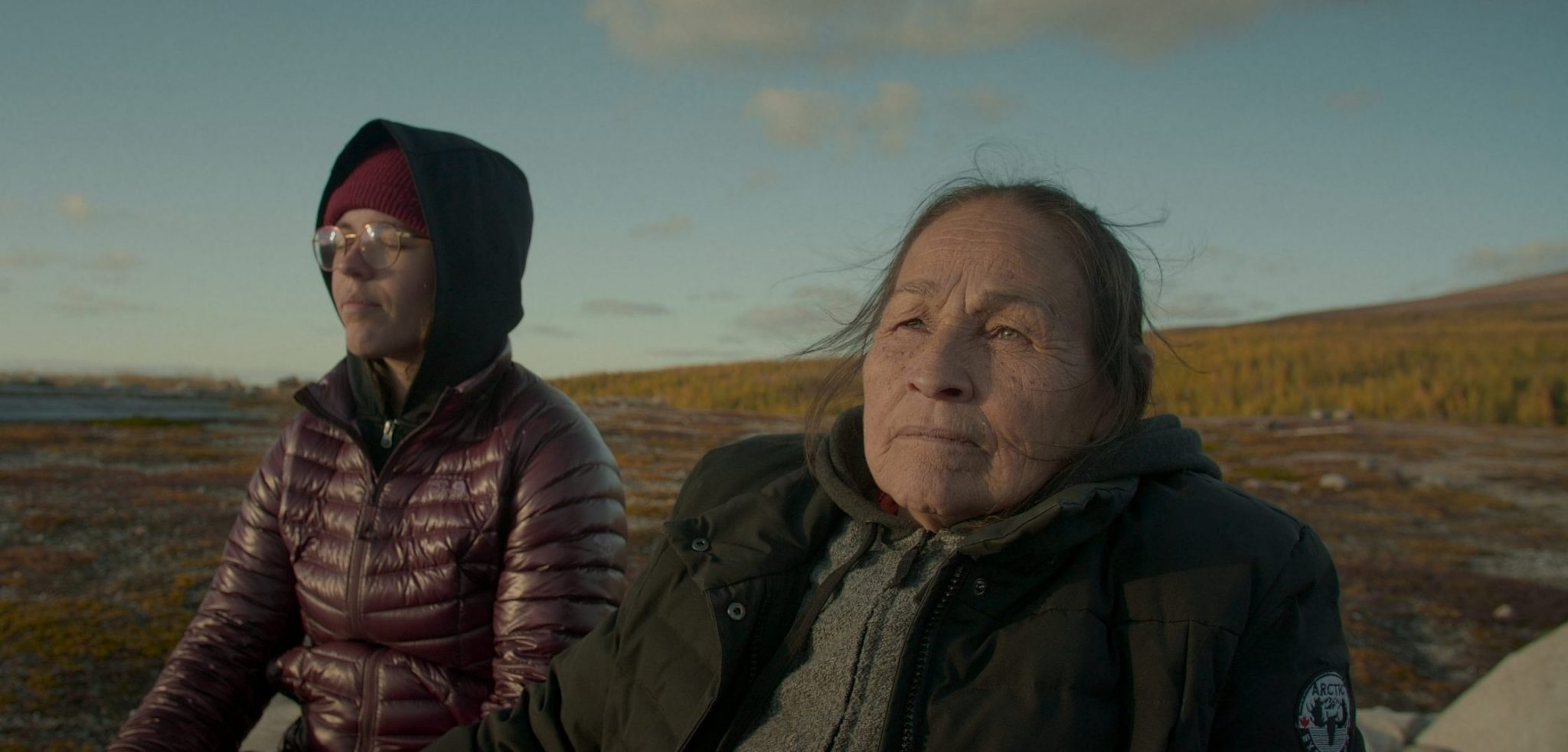 """A still from """"Call Me Human"""". Joséphine, the film's Innu protagonist, sits in the wilderness accompanied by another, younger person. Joséphine looks out into the horizon. The younger has a tranquil expression, with their eyes closed. Though there is a gentle light on their faces, they both wear large cold weather jackets."""