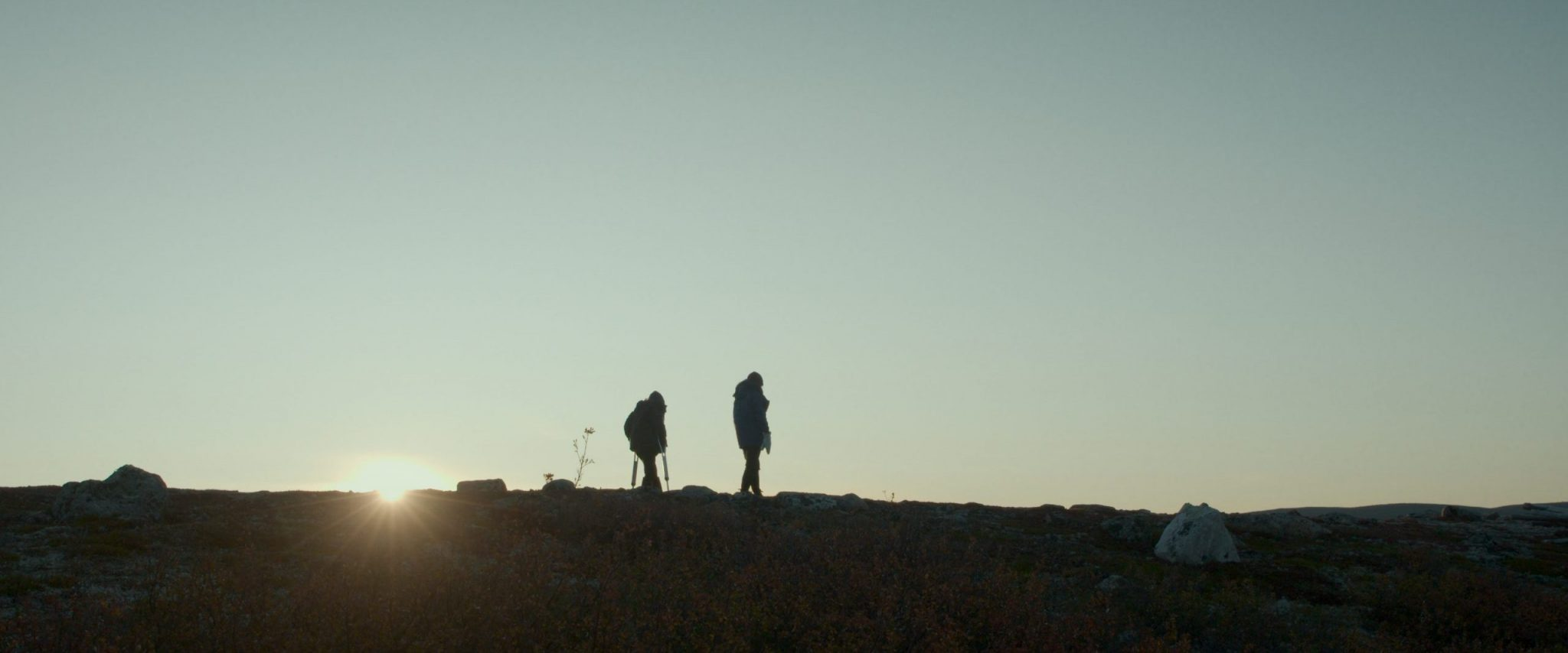 """A still from """"Call Me Human"""". A sillhouette of two people on a hilltop as the sun sets behind them on the left side of the frame. There are light rays spreading out from the disappearing sun, and beyond it the sky is a dusky blue, taking up most of the image. The two figures wear coats and hiking gear and appear to be on a journey."""