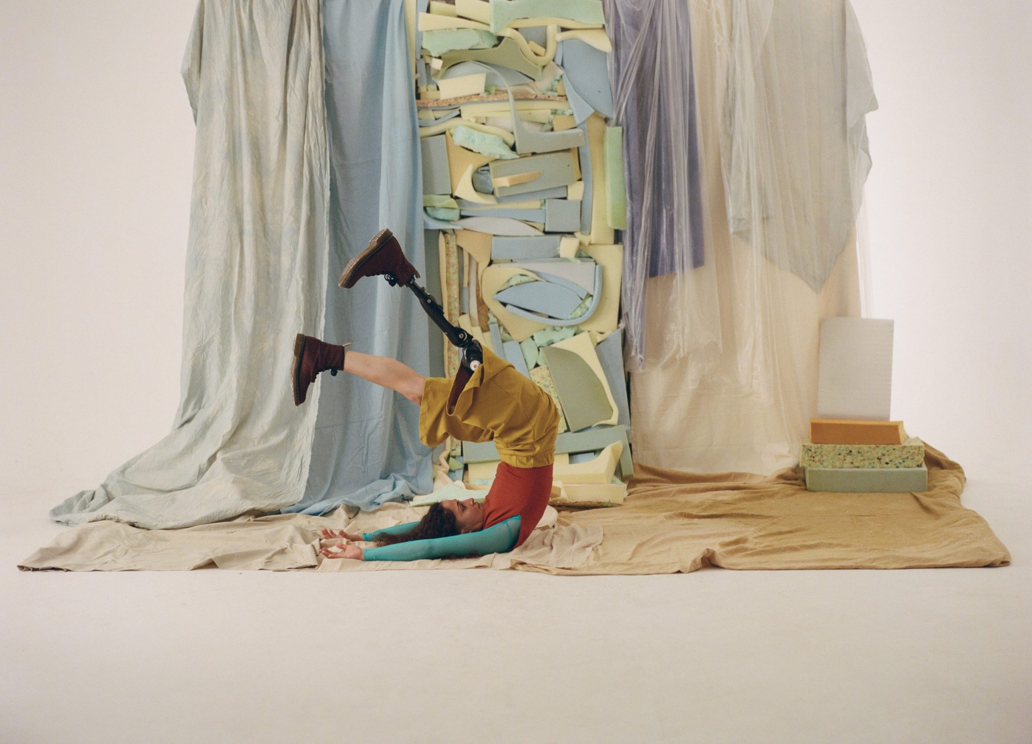 """A still from """"Material Bodies"""". A person on their back raises their legs in the air. They wear a prosthetic leg that is made of black metal. Behind and underneath them is a sculptural backdrop made of draped fabrics and shards of foam in faded colours including beige, purple, blue and green."""