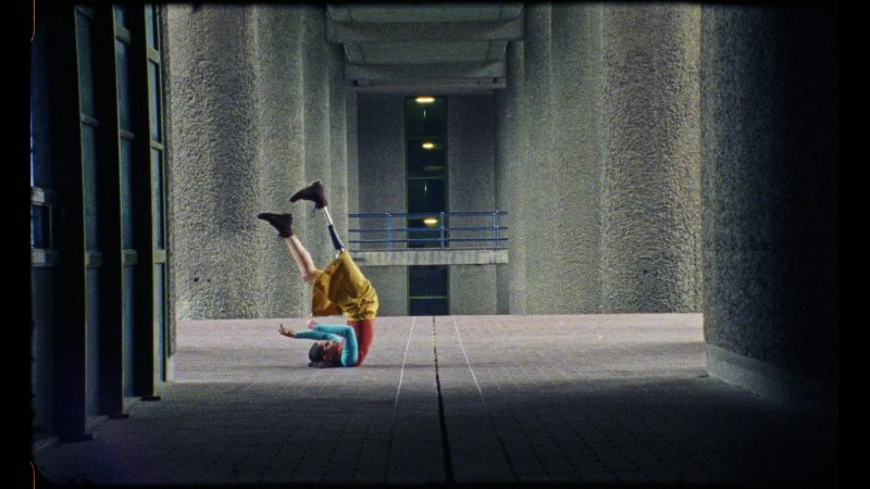 """A still from """"Material Bodies"""". In an outdoor space lined with concrete pillars, a person lies on their back, balancing on their shoulders and raises their legs in the air. They wear a prosthetic leg that is made of black metal."""