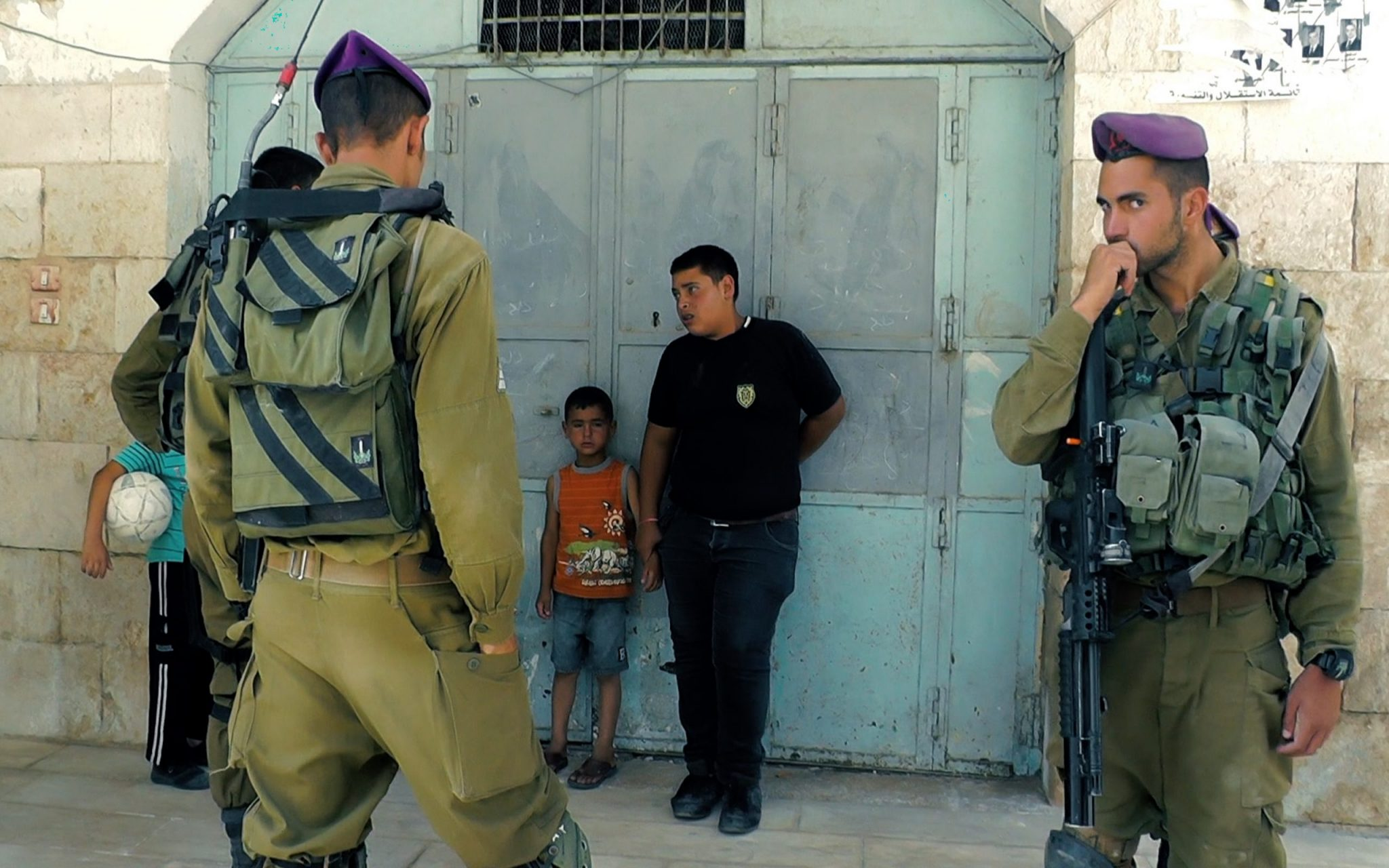"""A still from """"Of Land and Bread"""". Three armed soldiers wearing purple berets surround three children. The children have anxious expressions and stand against a blue metal door."""