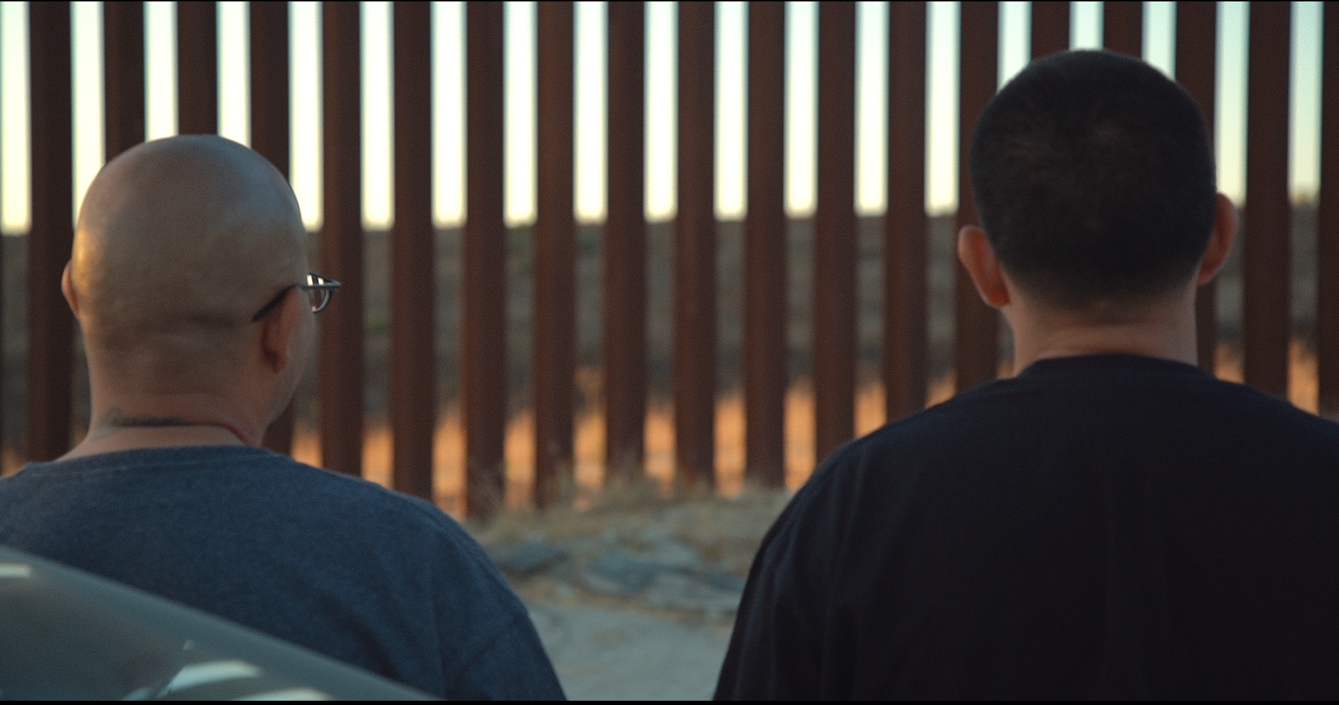 """A still from """"On The Line"""". Two people with close-shaved heads are looking away from the camera towards a tall barrier made of metal bars. Beyond the wall the sun sets over the desert."""