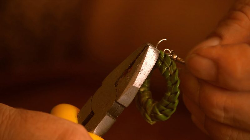 """A still from """"The Roots Weaver"""". A close up of two hands working on a small object. One hand holds metal pliers, whilst the other holds the end of an earring hook. They are fastening the hook to a small ring made of knotted grass."""