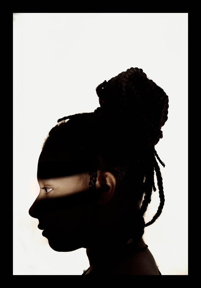 A side-profile headshot of artist Lilophilia against a white background. She has her braided hair up in a high bun and all of her face is in shadow except a strip across her eyes.
