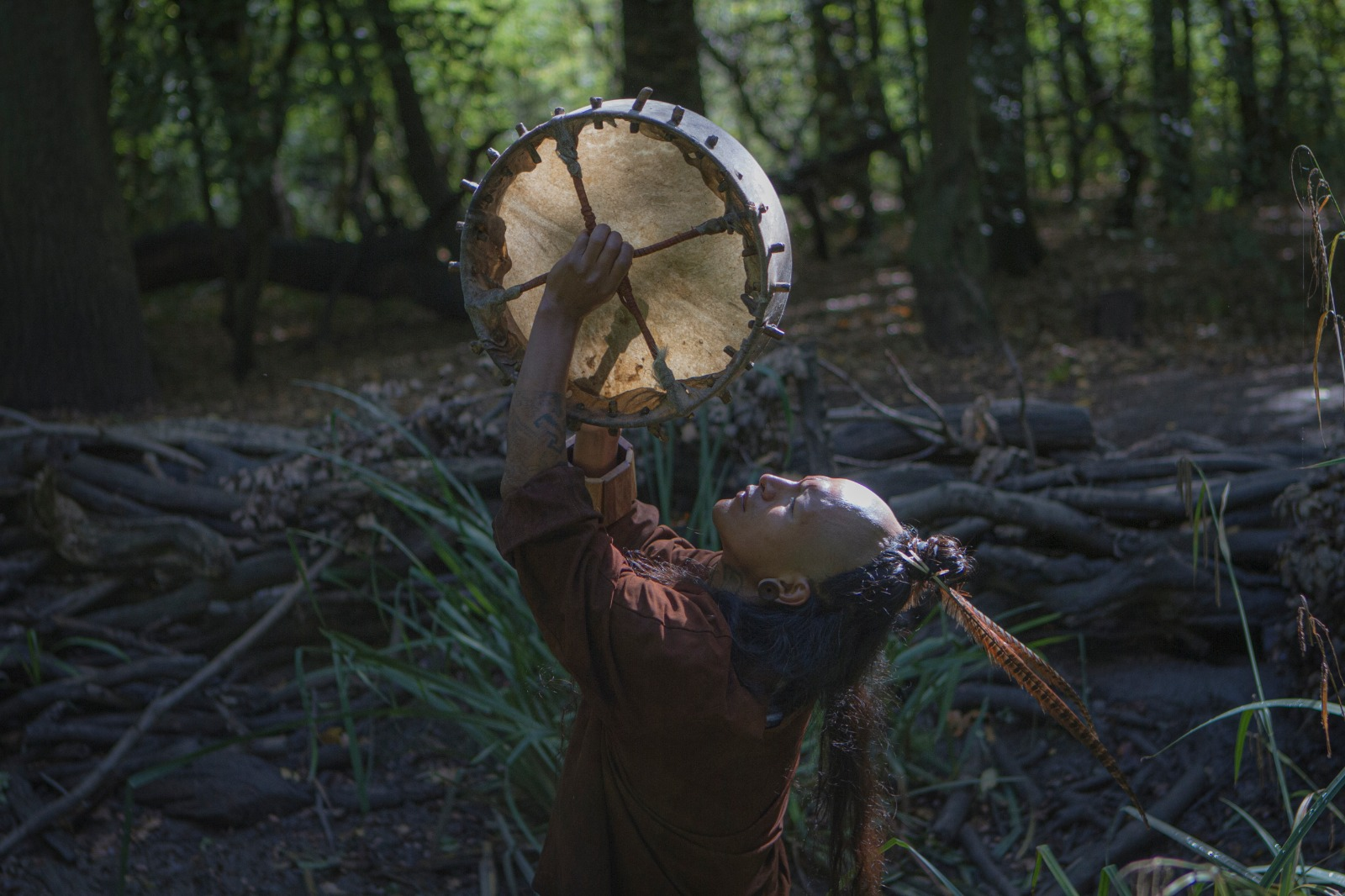 A person with long dark hair in a pony tail with a feather headdress stands in a forest and holds up a drum whilst leaning back and looking up.