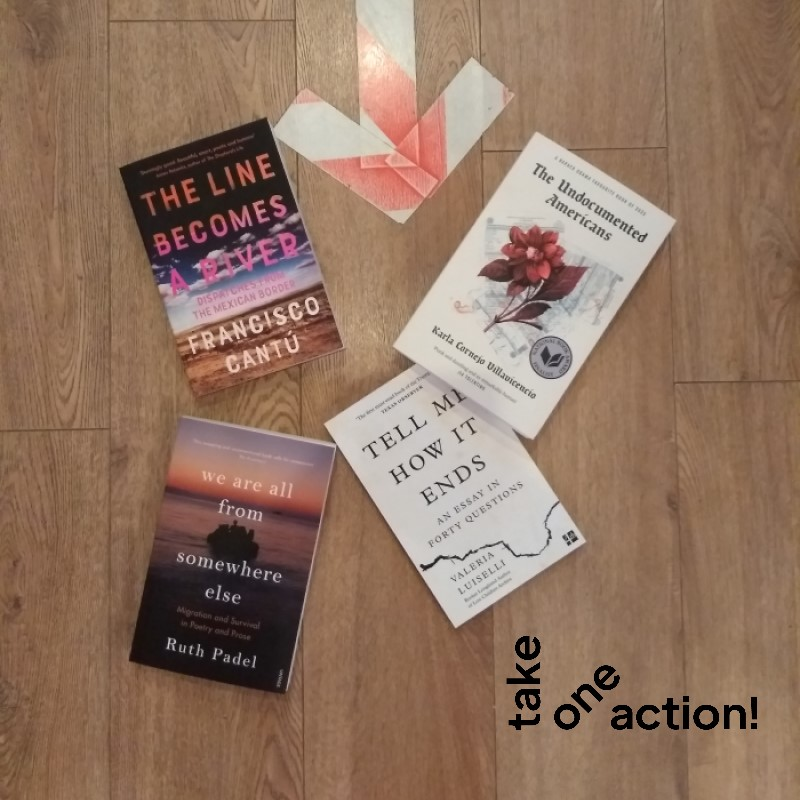 A selection of books on deportaiton and borders, laid out on a wooden floor.