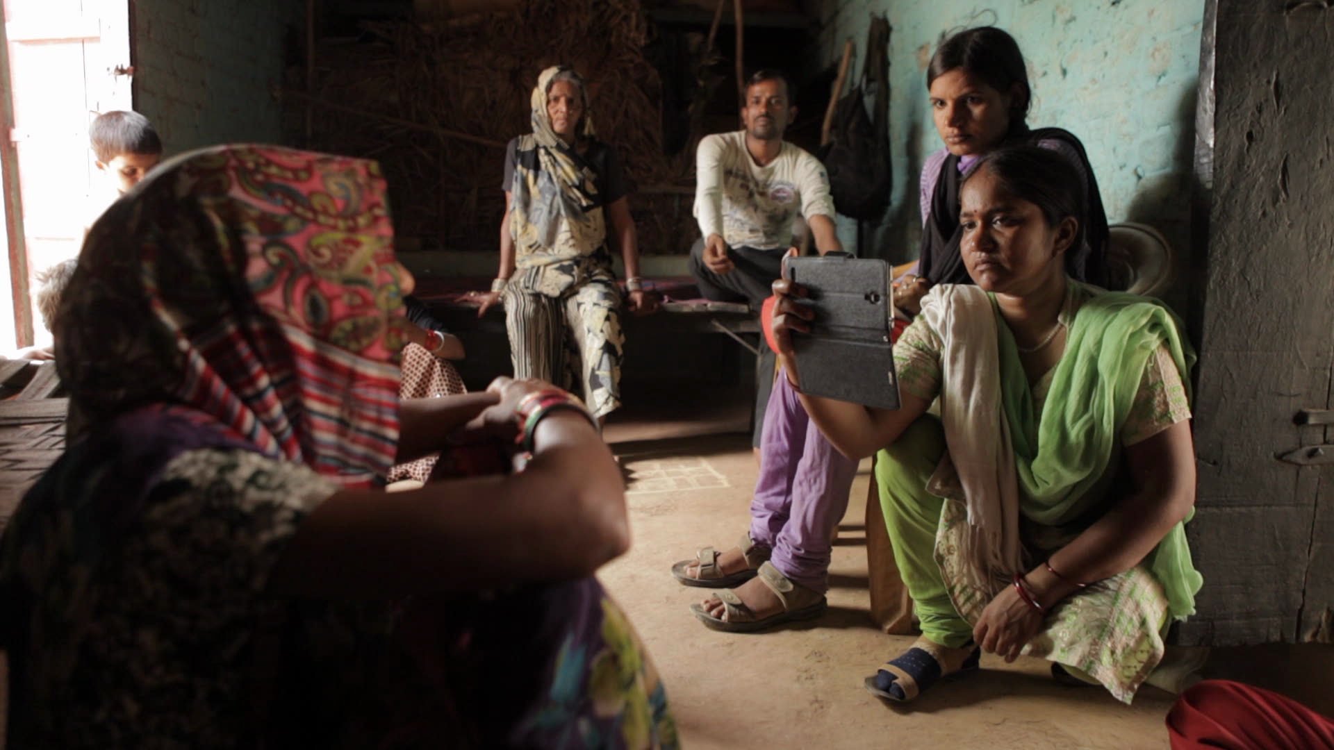 """Still from """"Writing with Fire"""". A person wearing a head covering looks away from the camera, woman wearing draped clothing and sandals crouches on the floor, holding up a smartphone to film them. Three adults and a child watch from behind. The walls and floor are bare, painted in washed out colours."""