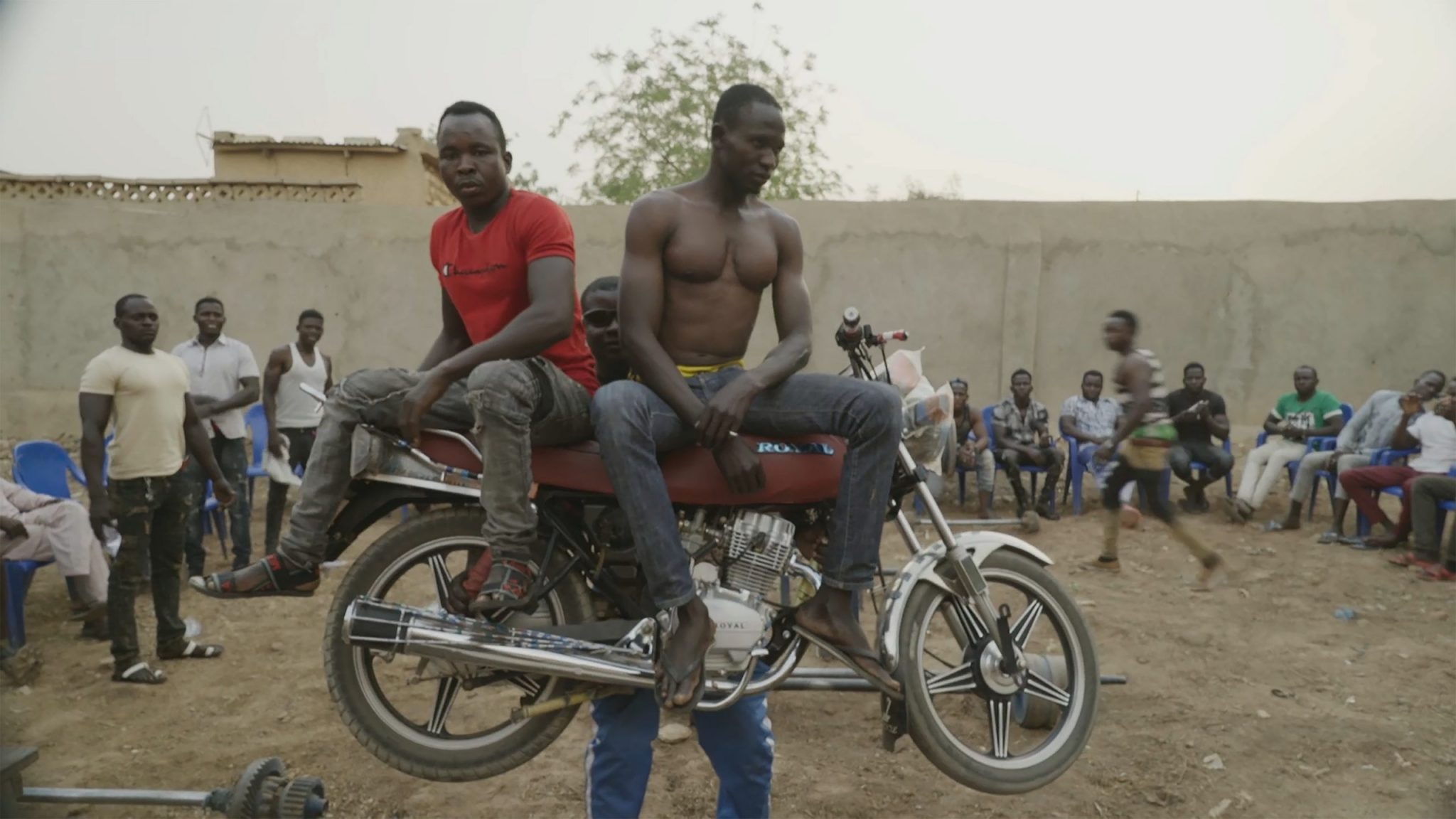 """Still from """"Zinder"""". In a dirt courtyard contained by a tall concrete wall, two men sit assertively atop a motorcycle held high above the ground by another man. Surrounding them are people standing and sitting in plastic chairs, watching the scene. Visible beyond the wall is a tree and the top of a low building."""
