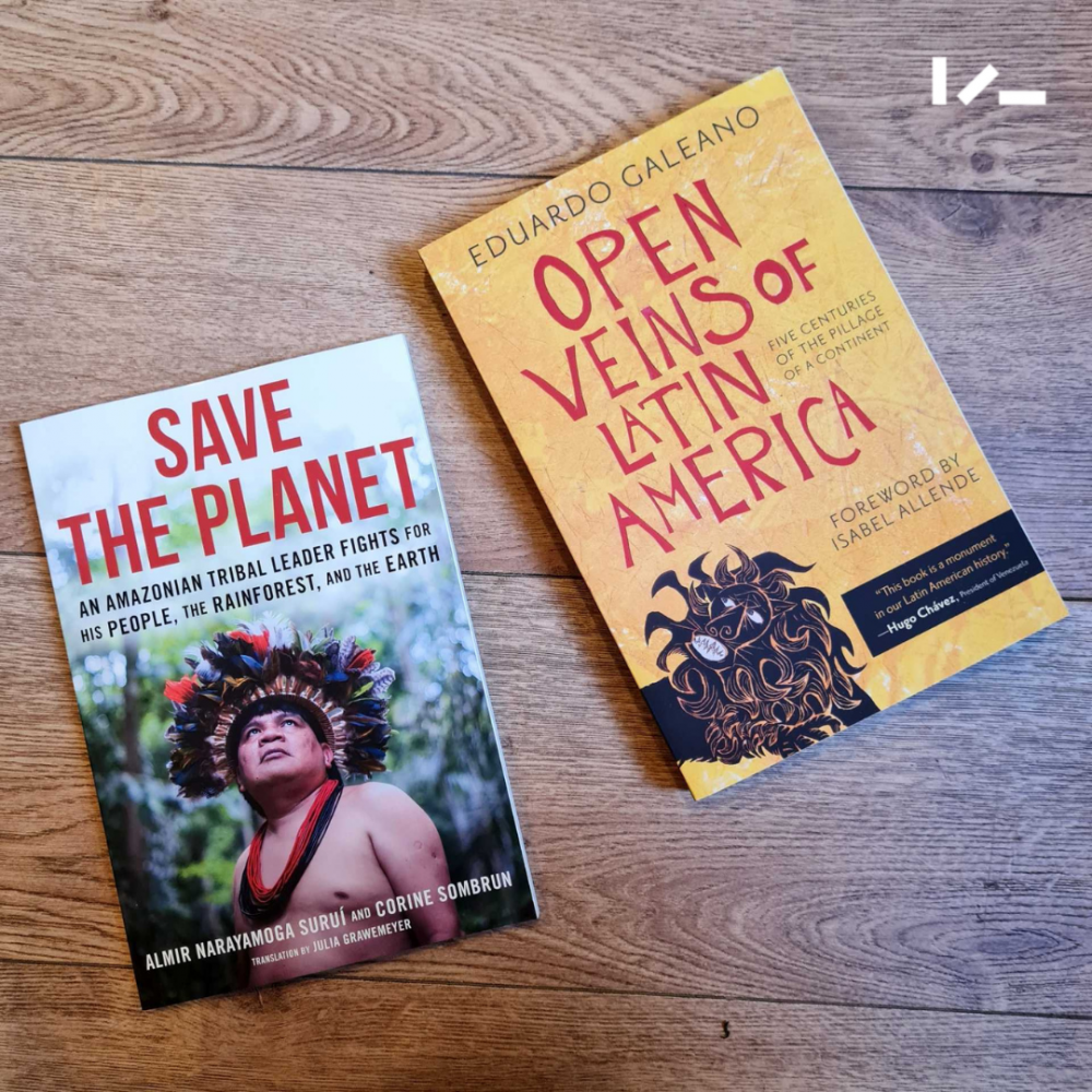 """Two books lying on a wooden floor - """"Save the Planet"""" and """"The Open Veins of Latin America"""""""